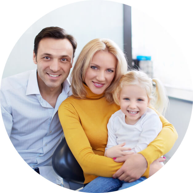 A couple with their young daughter sitting in a dentist office, all are smiling