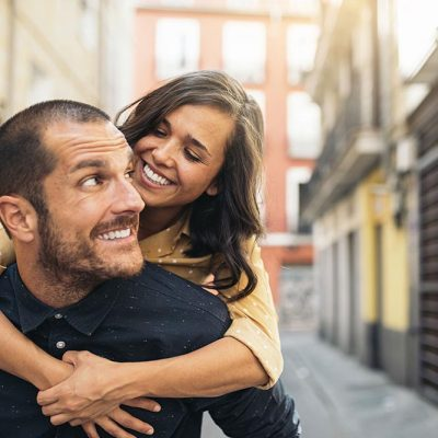 A woman getting a piggy back ride from her boyfriend walking down a city alley in Europe