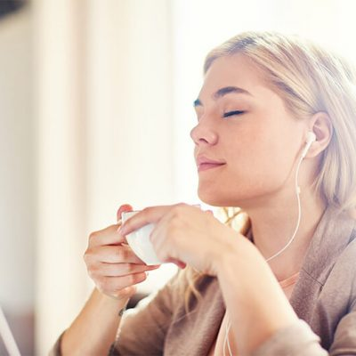 A woman with blonde hair drinking from a white coffee cup relaxing and listening to music with her eyes closed