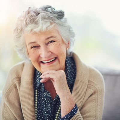 And older woman wearing a tan sweater sitting with her chin propped on her left hand