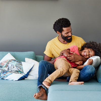 A father and his daughter playing on a blue couch