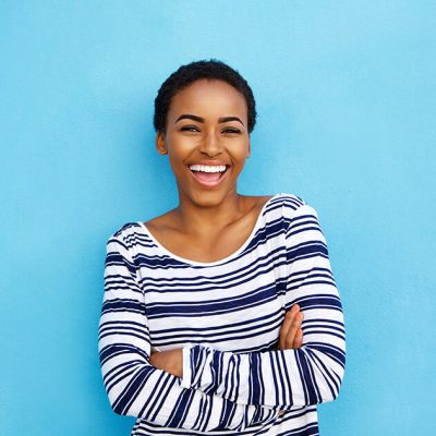 A smiling woman wearing a blue and white stripped shirt standing against a light blue wall