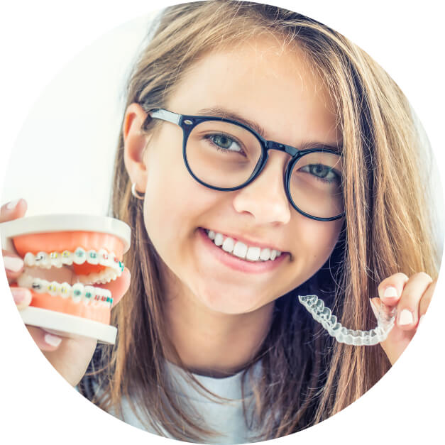 A girl with long hair and black glasses holding a clear Invisalign aligner and a model of the top and bottom teeth with colorful traditional braces