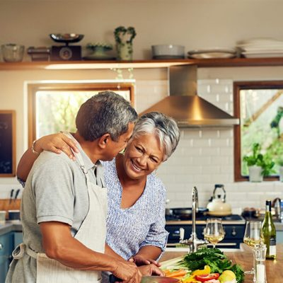 An older couple cutting vegetables, looking at each other and smiling