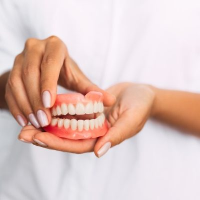 A woman holding a set of upper and lower dentures
