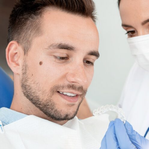 A dentist showing a patient a clear Invisalign aligner
