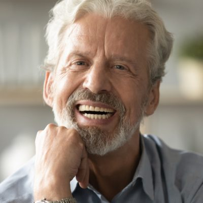 An older man with gray hair and beard smiling, showing his new dentures